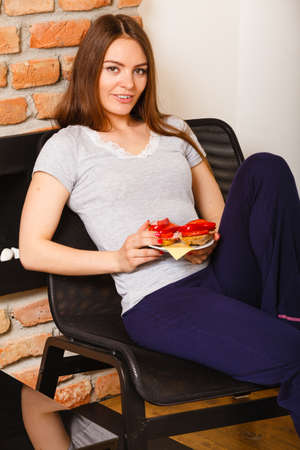 mornings: Mornings people concept. Attractive woman eating breakfast. Young lady has sandwich with vegetables.