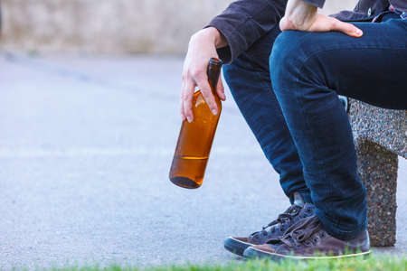 alcoholismo: Man depressed with wine bottle sitting on bench outdoor. People abuse and alcoholism problems.