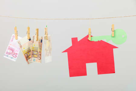 laundry concept: Red house with green key and banknotes cash hang on laundry line on grey background. Selling and buying home concept. Stock Photo