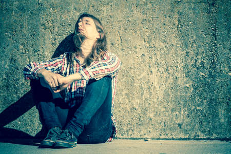 long depression: Man bearded long hair sitting sad alone by grunge wall outdoor. Unemployment depression or sadness concept.