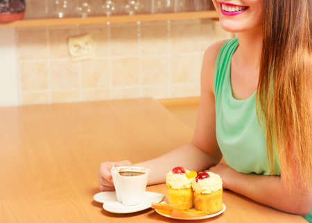 glutton: Woman with cup of coffee and delicious gourmet sweet cream cake cupcake and orange. Glutton girl sitting in kitchen with hot beverage having breakfast. Appetite and gluttony concept.