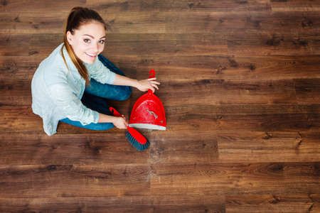high angle view: Cleanup housework concept. cleaning woman sweeping wooden floor with red small whisk broom and dustpan unusual high angle view