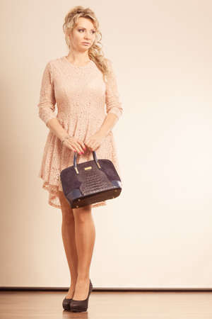 girly: Fashion, people concept. Nice, girly female with black handbag. Lady is wearing very girly dress and high heels.