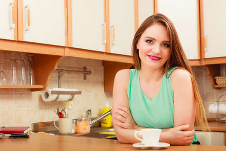 energizing: Woman sitting in kitchen with cup of coffee. Young girl and hot energizing beverage that keeps her awake. Energy and caffeine. Stock Photo