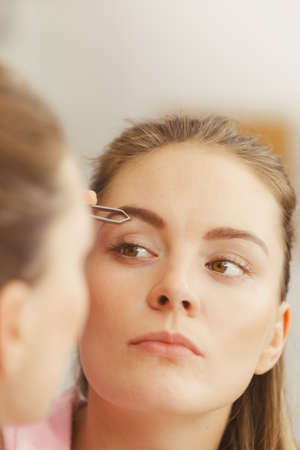 brows: Woman plucking eyebrows depilating with tweezers. Attractive girl tweezing eye brows looking in bathroom mirror.