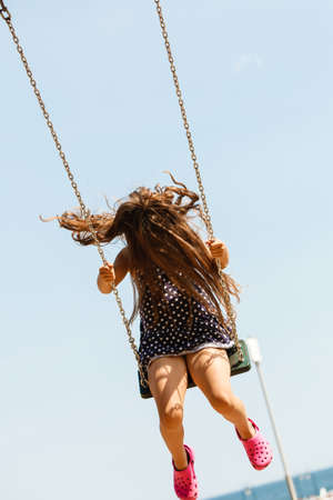 enjoyable: Have fun and leisure concept. Long haired enjoyable girl swinging outdoor in garden playground. Lovely child playing on swing-set. Stock Photo