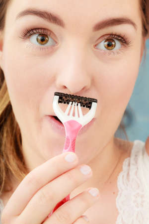 Woman shaving mustache with razor shaver. Young girl removing hair. Hygiene. Banco de Imagens
