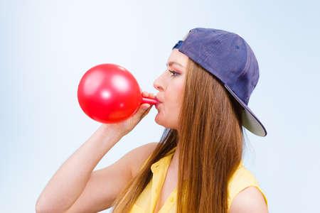Hora de fiesta. La mujer de moda joven prepara la decoración de la celebración del cumpleaños. Adolescente en tapa que sopla el globo rojo. Foto de archivo - 59890119