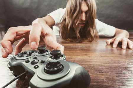 dependency: Addiction and dependency concept. Young man with pad joystick playing games. Male addicted to console  videogames.
