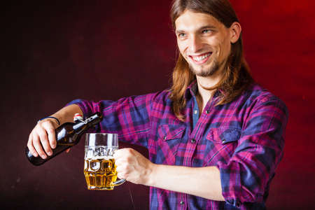 empties: Alcohol liquor drinking relax party concept. Tapster fills stein from bottle. Young male bartender empties beer into glass. Stock Photo