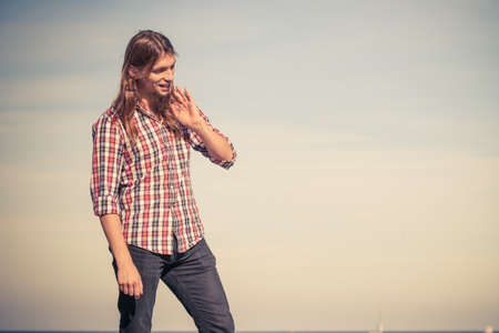 man long hair: Man long hair wearing plaid shirt relaxing outdoor at sunny windy day against blue sky