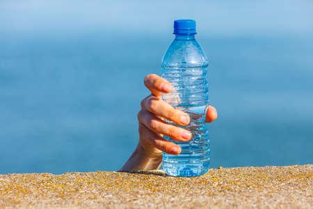 clear away: Male hand taking away water plastic bottle outdoor on sea shore