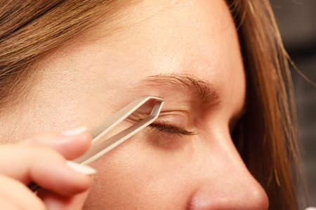 depilate: Woman plucking eyebrows depilating with tweezers closeup part of face. Girl tweezing eyebrows.