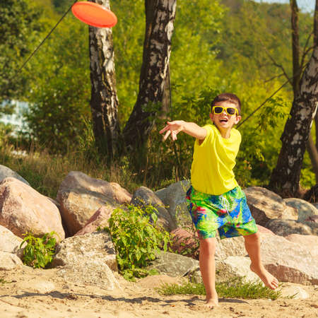 enjoyable: Play and fun concept. Little playful enjoyable boy kid throwing frisbee disc. Male child having fun playing outdoor on beach.