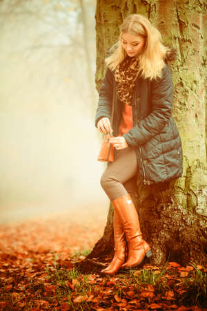 Woman with handbag walking relaxing in foggy day in romantic autumn forest park outdoor