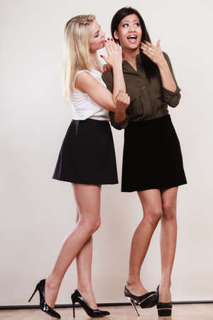 Two women multiethnic whispering and smiling, sharing their secrets, full length studio shot