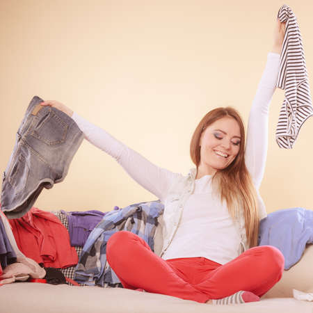 messy clothes: Happy woman sitting on sofa couch in messy living room holding clothes. Young girl surrounded by many stack of clothing. Disorder and mess at home.