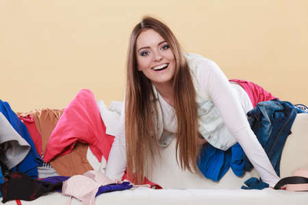 habitacion desordenada: Happy woman picking clothes up off sofa couch in messy living room. Young girl surrounded by many stack of clothing. Disorder and mess at home.