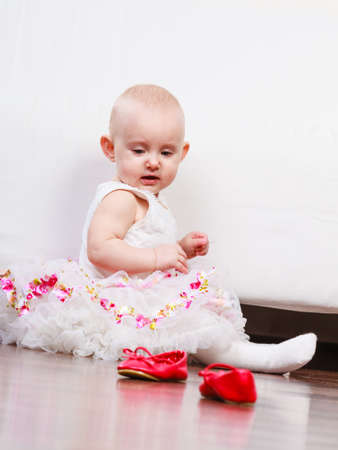 girl squatting: Lesson of walking. Sweet adorable baby girl thinking about make step. Little child toddler wearing princess dress with red small shoes. Stock Photo