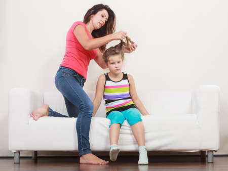 combing: Mother combing daughter, care about hairstyle. Girl is unhappy mom pulling her hair. Important role in child life.