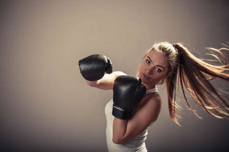 intimidating: Energy fighting boxing with opponent. Sports and bodybuilding. Strong young woman punch enemy. Girl with ponytail wear white tank top and boxing gloves.