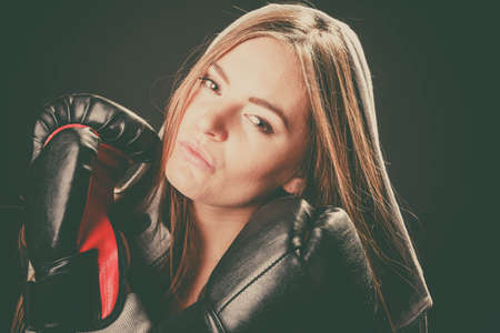 intimidating: Exercising prepare for fight. Sportsmanship and strong body. Young woman wear sportswear and boxing gloves. Stand with crossed hands look at opponent defend.