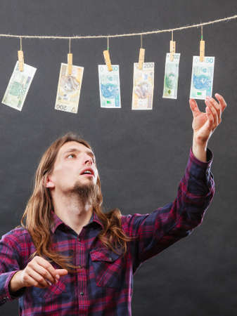 verify: Currency exchange concept. Man worker check verify money cash. Payment hang on laundry line. Stock Photo