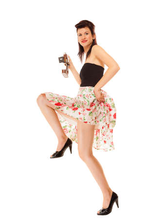 Beautiful photographer. Full length pretty retro style summer teen girl holding using vintage old camera isolated on white background