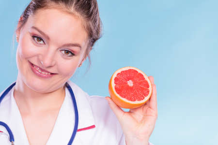 promoting: Happy dietitian nutritionist holding grapefruit. Woman promoting healthy food fruit. Right eating nutrition and slimming concept.