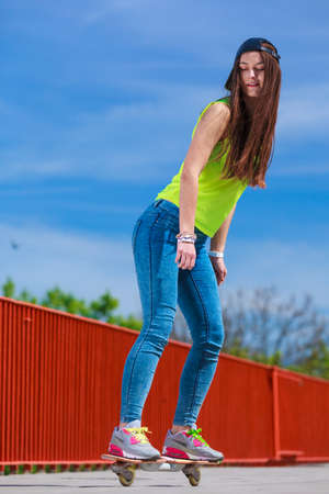 skateboarder: Summer sport and active lifestyle. Cool teenage girl skater riding skateboard on the street. Outdoor.