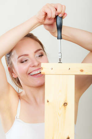 enthusiast: Woman assembling wooden furniture using screwdriver. DIY enthusiast. Young girl doing home improvement.