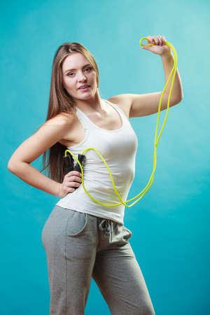 saltar: apta joven mujer delgada pasar el tiempo libre de forma activa. Belleza niña deportivo con ropa deportiva con saltar la cuerda de saltar sobre fondo azul.