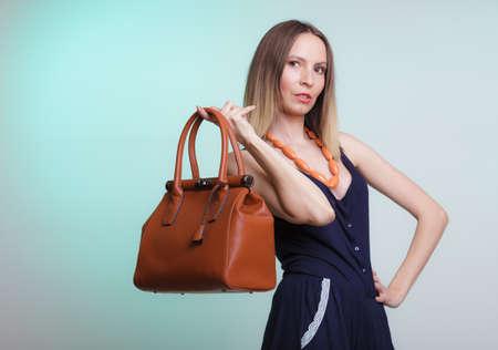 Elegant fashionable woman with leather handbag. Stylish girl on green holding brown bag. Women fashion vogue. Studio.