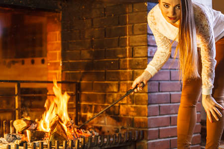 fireproof: Woman with fire iron poker at fireplace. Young girl heating warming up and relaxing. Winter at home.