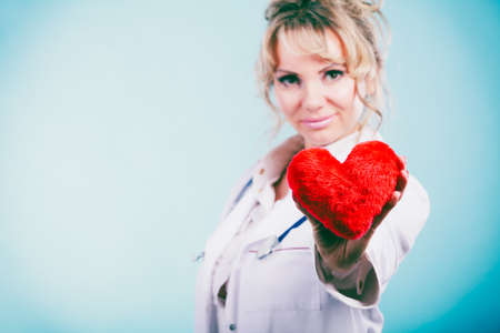 heart work: Love from working and helping people. Mid age blonde doctor in white medical apron with heart on blue. Enjoy work concept. Stock Photo