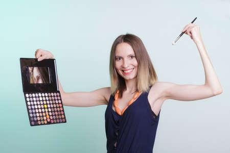 and eyelid: Woman stylist applying eyeshadow with professional makeup palette and brush. Girl beautyfying eye eyelid. Make up makeover concept.
