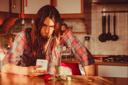 desilusion: La decepción y la depresión. el concepto de amor no correspondido. Hombre joven preocupante decepcionado con Rosa roja, smartphone telefono esperando a su novia.