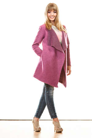 Fashion. Young blonde fashionable woman in vivid color pink coat. Female model posing isolated on white background Stock Photo