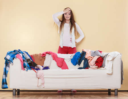 messy clothes: Desperate helpless woman standing behind sofa couch in messy living room with hand on head. Young girl surrounded by many stack of clothes. Disorder and mess at home. Stock Photo