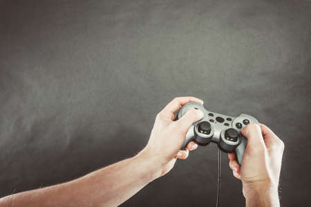 playstation: Playing games concept. Part body man with joystick play game on console playstation. Male hands holding grey pad. Stock Photo