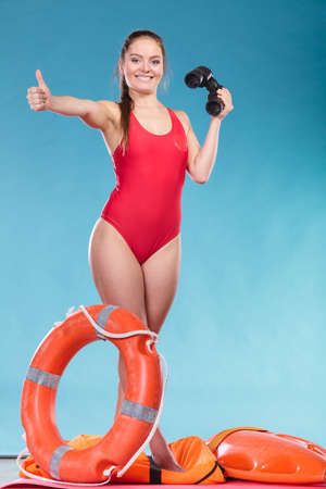 Happy lifeguard with ring buoy lifebuoy and binoculars. Woman girl supervising swimming pool water on blue. Accident prevention. Stock Photo
