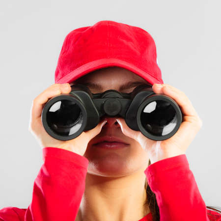 Accident prevention and water rescue. Closeup girl in red lifeguard outfit on duty looking through binocular on gray Stock Photo