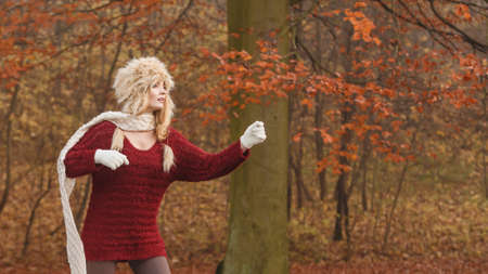 Fashion woman with flying scarf in windy fall autumn park forest against blowing wind. Young girl posing in fur cap and sweater having fun outdoor. Stock Photo