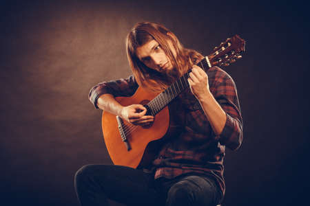 chords: Guitarist trying out chords. Young male musican practicing on guitar. Music instrument passion concept. Stock Photo