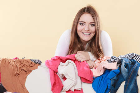 living things: Happy woman behind sofa couch in messy living room. Young girl surrounded by many stack of clothes. Disorder and mess at home. Stock Photo