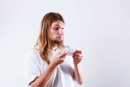 snot: Allergy and cold concept. Young long haired sick man with hygienic tissue. Guy blowing nose.
