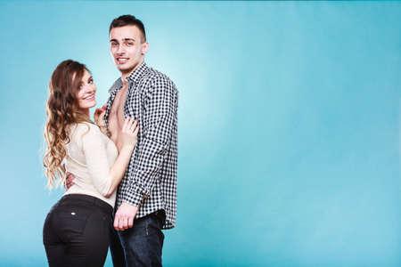 Portrait of smiling woman and man posing in studio on blue. Happy joyful couple. Good relationship.
