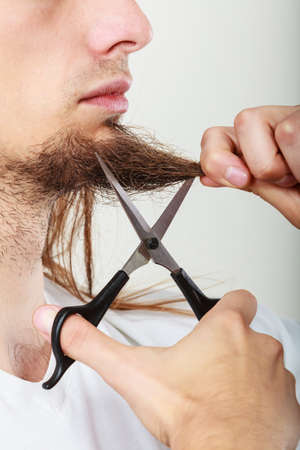 hair part: Cut and shave concept. Young man with long beard holding scissors. Part face boy cutting hair on chin.