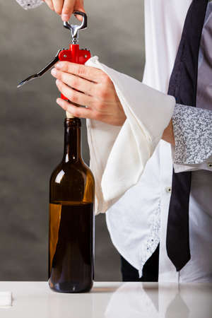 sommelier: Winery serving tasting alcohol liquor concept. Waiter opens wine bottle. Young male sommelier pulls out cork.