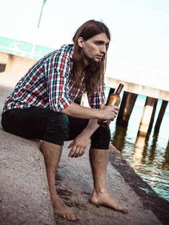 alcoholismo: Hombre deprimido con la botella de vino sentado en la orilla del mar al aire libre. La gente abuso y problemas de alcoholismo